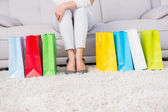 Woman on couch with shopping bags — Stock Photo
