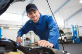 Mechanic examining under hood of car — Stock Photo