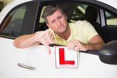 Man gesturing thumbs down holding a learner driver sign — Stock Photo