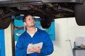 Mechanic examining under the car — Stock Photo