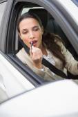 Pretty businesswoman using wing mirror to put on lipstick — Stock Photo