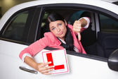 Woman gesturing thumbs down holding a learner driver sign — Stock Photo