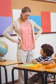 Angry teacher looking pupil with hands on hips — Stock Photo