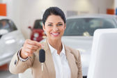 Smiling saleswoman giving customer car key — Foto de Stock