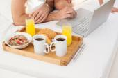 Young couple having breakfast in bed — Stock Photo
