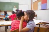 Cute pupils whispering in classroom — ストック写真
