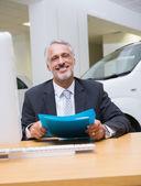 Uomo d'affari sorridente che tiene una cartella al suo scrittorio — Foto Stock
