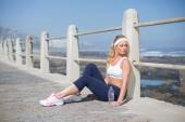 Fit blonde sitting on the pier — Foto Stock