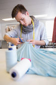 Student cutting fabric with pair of scissors  — Stock Photo