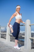 Fit blonde stretching on the pier — Stock Photo