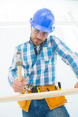 Carpenter hitting nail on wooden plank  — Stock Photo