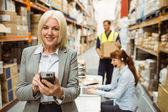 Smiling warehouse manager using handheld — Stock Photo