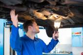 Mechanic using torch to look under car — Stock Photo