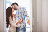 Couple kiss as they open front door — Photo
