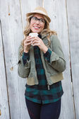 Blonde in hat holding disposable cup — Stock Photo