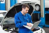 Mechanic using his laptop — Stock Photo