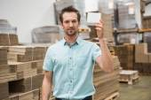 Warehouse worker showing small box — Stock Photo