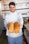 Baker showing loaves of bread — Stock Photo