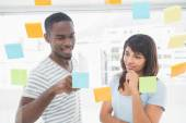 Smiling coworker reading sticky notes — Stock Photo