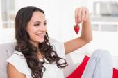 Brunette eating strawberries on couch — Stock Photo