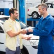 Customer shaking hands with mechanic — Stock Photo #65540881