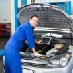 Mechanic examining under hood of car — Stock Photo #65542075