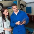 Mechanic showing tablet pc to customer — Stock Photo #65542083