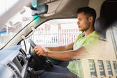 Serious delivery man driving his van — Stock Photo