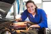 Mechanic smiling at the camera with torch — Stock Photo