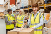 Smiling warehouse workers preparing a shipment — Stock Photo