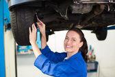 Smiling mechanic adjusting the tire — Stock Photo