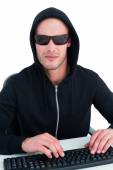 Stern hacker with sunglasses typing on keyboard — Stock Photo