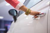 Woman holding a car door handles — Stock Photo