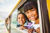 Cute pupils smiling at camera in the school bus — Stock Photo