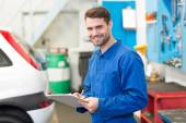 Mechanic writing on a clipboard — Stock Photo