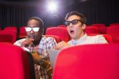 Astonished young friends watching 3d film — Stock Photo
