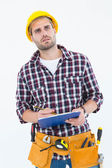 Thoughtful male repairman writing on clipboard — Stockfoto