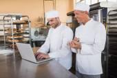 Uśmiechnięty piekarzy wspólnej pracy na laptopie — Zdjęcie stockowe