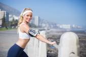 Fit blonde listening to music warming up — Stock Photo