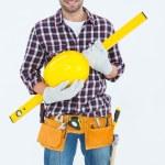 Handyman holding hard hat and spirit level — Stock Photo #65551961