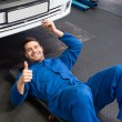 Mechanic lying and working under car — Stock Photo #65553249