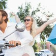 Cute couple riding a scooter — Stock Photo #65553471