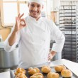 Happy baker showing tray of rolls — Stock Photo #65554441