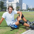 Fit man getting ready to roller blade — Stock Photo #65554751