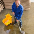 Smiling man moping warehouse floor — Stock Photo #65555743