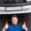 Mechanic lying and working under car — Stock Photo #65555759