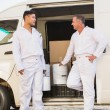 Painters smiling leaning against their van — Stock Photo #65556379