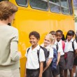 Cute schoolchildren waiting to get on school bus — Stock Photo #65556619