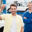 Customer and mechanic smiling at camera — Stock Photo #65557227