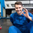Mechanic lying and working under car — Stock Photo #65557483